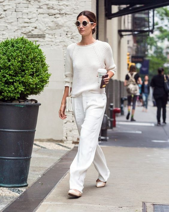 Lily Aldridge wears a white sweater, loose white trousers, ballet flats, and white accessories