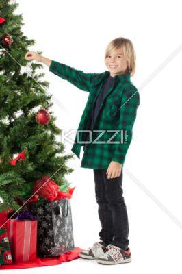smiling pre-adolescent boy decorating christmas tree. - Portrait of a smiling pre-adolescent boy decorating christmas tree, Model: Josh Chapman