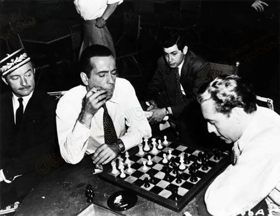 """Every chess player knows the famous scene in """"Casablanca"""" with Humphrey Bogart in front of a chessboard, but here is one off-camera, on the set of the film. In it Claude Rains (left) watches the usual suspects, Humphrey Bogart and Paul Heinreid, play a game.:"""