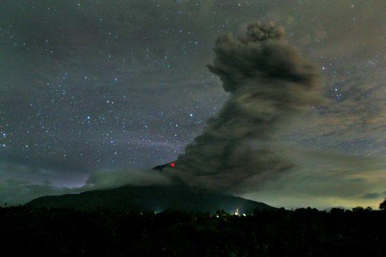 Fotografia tirada na noite de domingo (24) mostra a fumaça negra expelida pelo vulcão Sinabung, na Ilha de Sumatra, na Indonésia, em contraste com o céu estrelado - http://epoca.globo.com/tempo/fotos/2013/11/fotos-do-dia-25-de-novembro-de-2013.html (Foto: AP Photo/Binsar Bakkara)