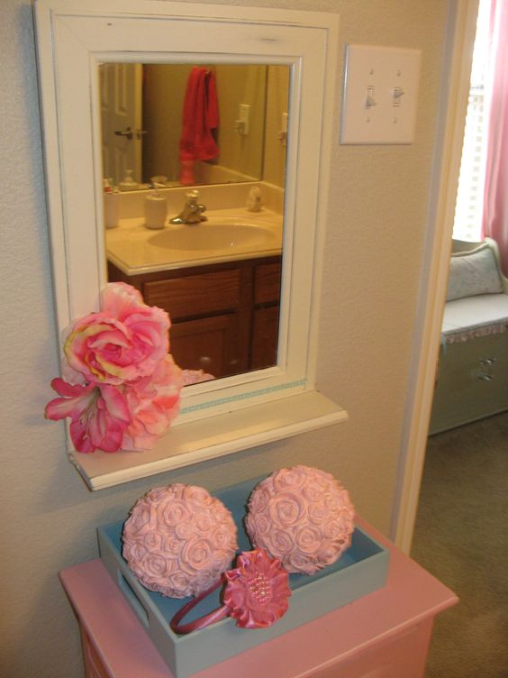 Got the mirror at a garage sale for $3. Painted it and added some flowers.  Found the rose balls in the wedding section at Hobby Lobby and paited those.  Little tray is from the dollar spot at Target.  Pink stand is from trash.  Total cost for this whole getup was about $20.