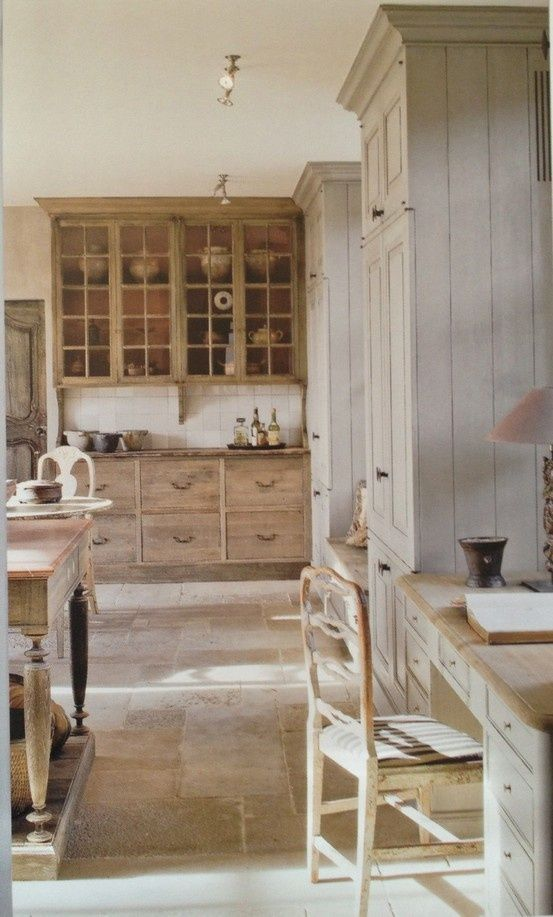 A breathtaking kitchen with French farmhouse decor including limestone flooring, rustic wood cabinetry in grey tones, antiques, and sophisticated style. #Frenchfarmhouse #Frenchcountry #kitchendecor #kitchendesign #rusticdecor #kitchenideas #interiordesignideas #sophisticated #European #antiques #France