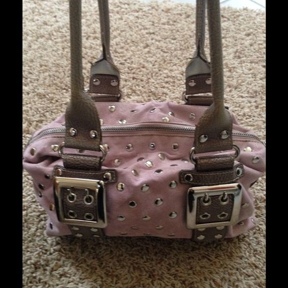 Pink Kathy Van Zeeland bag Soft pink/mauve shimmery material with silver studs and silver buckles. Brown handles. Used with love.  The outside of bag is in very good condition, the inside does show glue marks along the zipper, as this bag is a few years old. Would make a great starter bag. Kathy Van Zeeland Bags