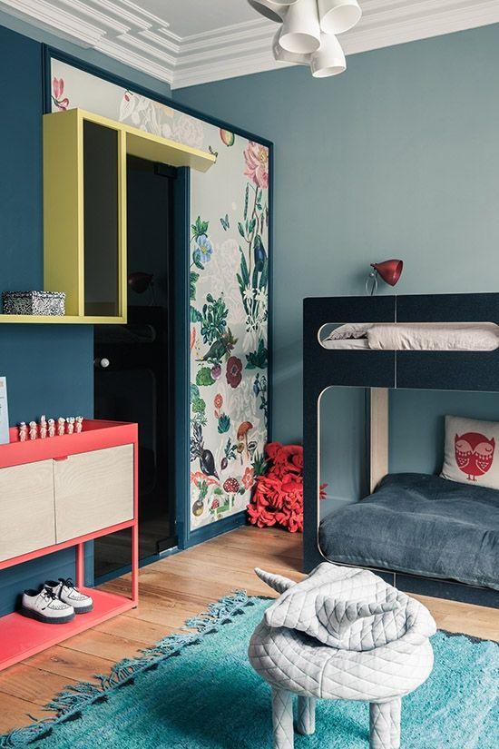 Chambre avec des nuances de bleu-vert avec tapisserie décalée, pouf en forme d'animal.