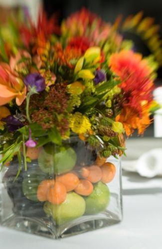 bright arrangement in vase filled with fruit,
