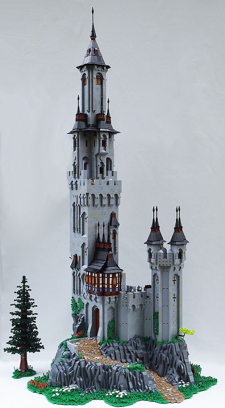 A tall tower stands alone in the woods, looming