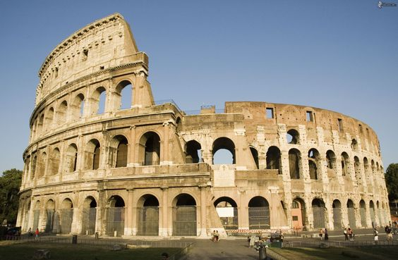 """Anfiteatro Flavio - 70/74, inaugurato 80 - Roma Fu costruito nel luogo in cui si trovava la Domus Aurea di Nerone, distrutta come """"damnatio memoriae"""".  Tradizionalmente riconosciuto come il simbolo di Roma, fu tuttavia fino al Settecento usato come cava di materiale edilizio.  Ci dimostra anche quanto fossero importanti per i Romani gli anfiteatri, costruiti come una sorta di doppio teatro in cui tuttavia si facevano spettacoli di giochi gladiatori o naumachie."""