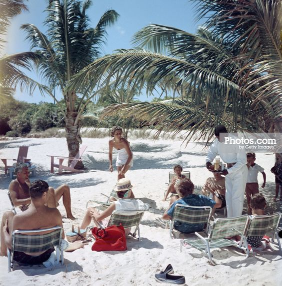 A waiter serves drinks on the beach at the Mill Reef Club on Antigua in the West Indies, 1960.: