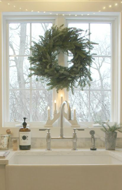 White kitchen ideas in photos we can't stop pinning! White kitchen with minimal modern European farmhouse style, LG Viatera quartz in Minuet, farm sink, and fresh green wreath with fairy lights. #holidaydecor #whitekitchen #hellolovelystudio #farmsink #swedish #farmhousekitchen #modernfarmhouse