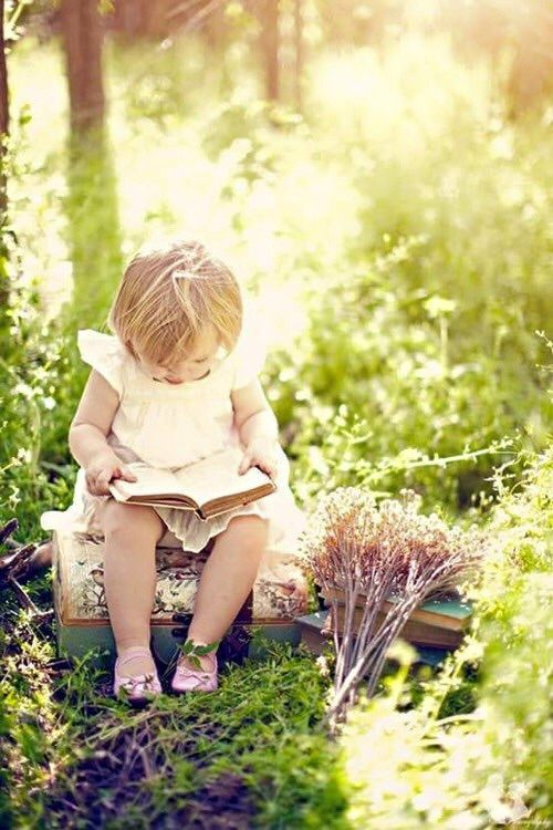 Young toddler child in pink shoes reading a book in lush green garden. #child #reading #garden #peaceful