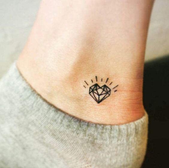 Tatuagem com traços simples de um diamante em forma de coração::