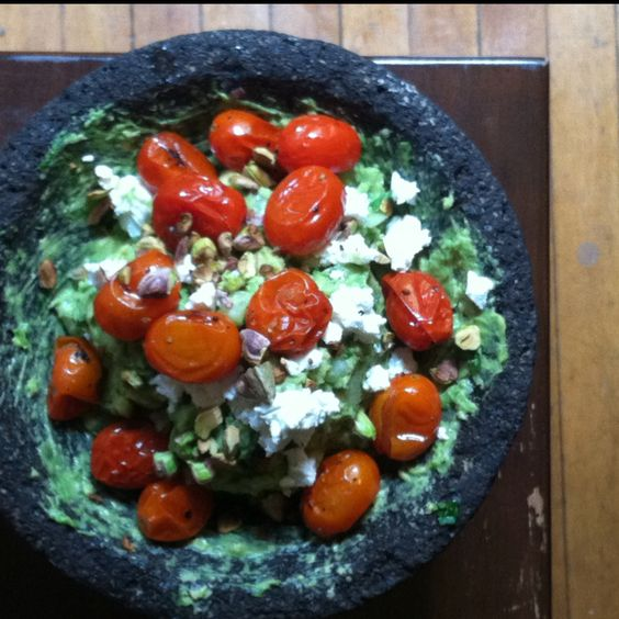 Guacamole with roasted tomatoes, goat cheese and crushed pistachios.