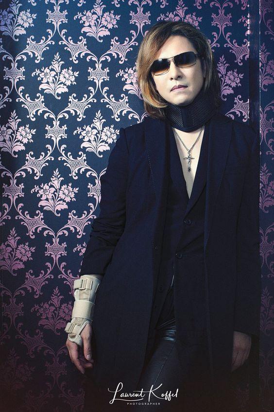 黒い衣装を着て壁にもたれかかっているXJAPAN・YOSHIKIの画像