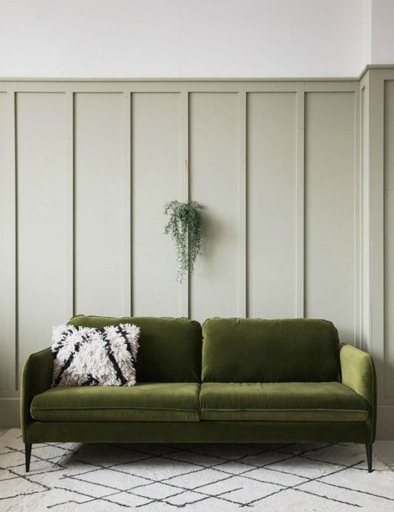 Warm khaki green painted board and batten paneling with green velvet sofa.