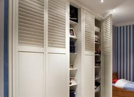 White Painted Louvre Wardrobe Doors Along One Wall Doors