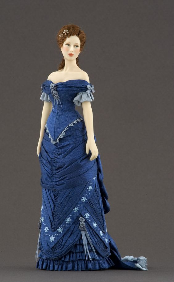 NAME: Anne  PERIOD: 1880-1883  PRICE: 550 euros  Silk dress inspired by an engraving published in the feminine magazine La Moda Elegante. It is profusely trimmed with silk thread embroideries and draperies.