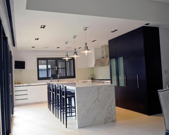#CamelotHomes   Pepperfields Project. Another modern kitchen design featuring stone bench tops and island with a holistically monochrome colour palette. You wouldn't think that there is a expansive walk-in pantry hiding behind the glass-panelled pantry doors.