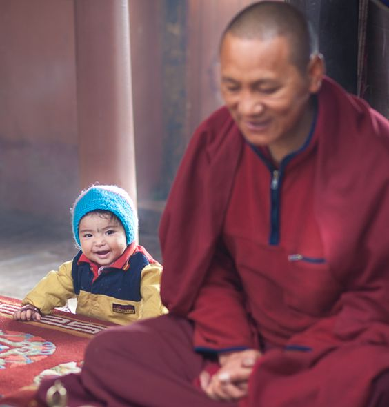 Even Buddhist monks are susceptible to the charms of a bubbly toddler who decides, with no hesitation whatsoever, to get the monk's attention. At the Stok Palace monastery in Ladakh, India.