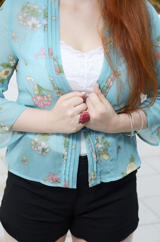 Blue sheer cardigan with a floral print. A white tank top with high waisted black shorts with scalloped hem & a hot pink leather flower ring #fashion #TwinVogue #Floral
