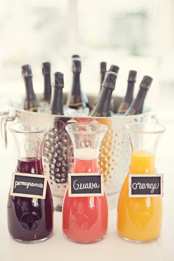 Three carafes filled with pomegranate, guava, and orange juice and guests choose which one to mix with their bubbly. A berry skewer with a cute tag attached is placed in each champagne glass.