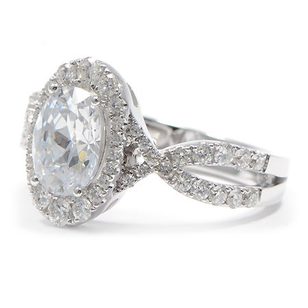 This engagement ring features a unique setting that is highlighted by a beautiful oval center diamond and intersecting loops that create a twisted shank.
