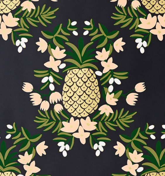 The Pineapple Ebony wallpaper features metallic gold pineapples, soft pink flowers, and green leaves printed on ebony paper | Rifle Paper Co.
