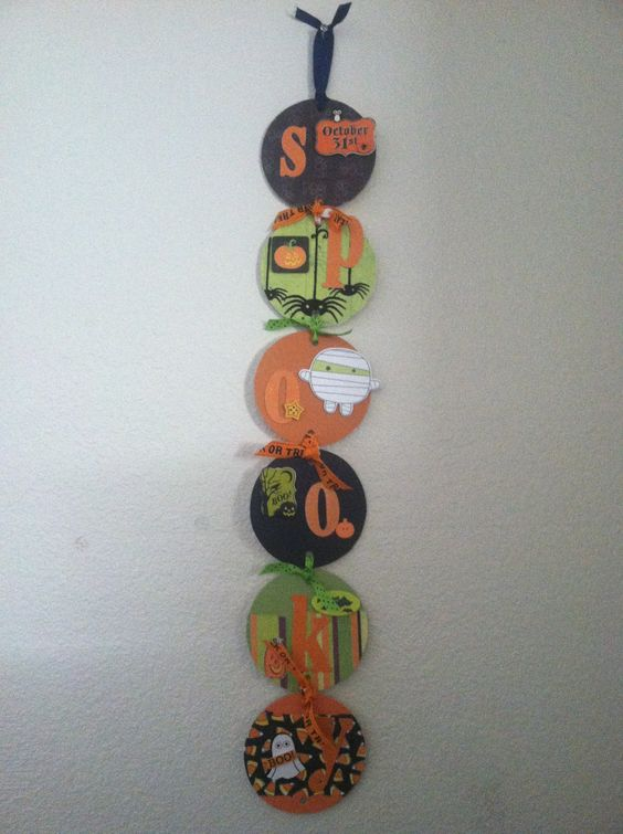 Super cute Halloween decoration my mom made!  Chip board circles, Halloween scrapbook paper, die cuts and ribbons!  So simple!