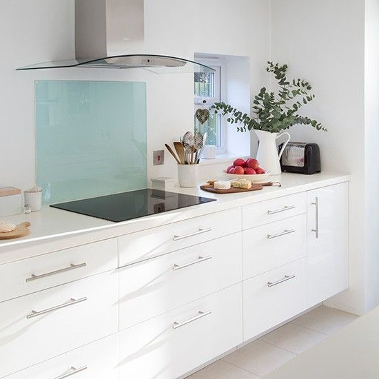 White gloss kitchen with blue glass splashback. Come and see this colour combination in our showroom!