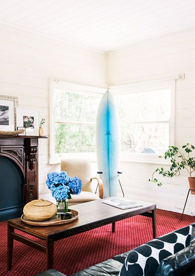 21 Homes That Prove Surf Is Chic // surfboards as decor // living room, wooden art decor fireplace mantel, black leather sofa, wooden coffee table, plant stands, cream walls