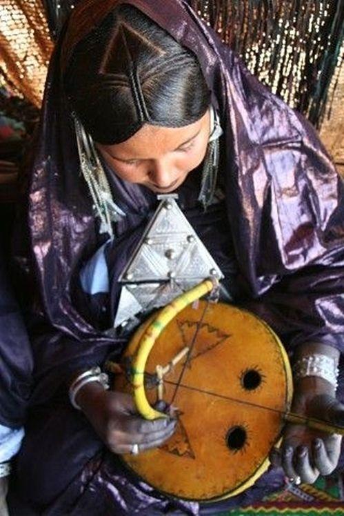 woman playing an unusual handmade instrument