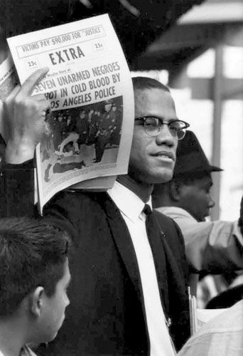 Gordon Parks - Malcolm X holding up Black Muslim newspaper., Harlem, New York, 1963