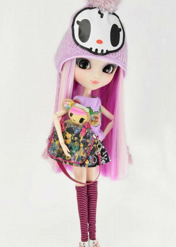 Esta es una kawaii muñeca de TokiDoki con tatuajes, viene con 3 diseños de ropa (3 pares de zapatos, 3 camisetas, y 3 faldas) tambien viene con 5 bolsos un gorro de lana 2 mini peluchitos un par de polainas y tatuajes para pegar