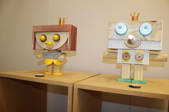 Papelão ondulado e micro ondulado, pedaços de madeira e lâmpadas de LED compõe a coleção de Toy Art do Studio Midaglia. O casal dos simpáticos bonequinhos com roupa de rei e rainha se destacam no estande.
