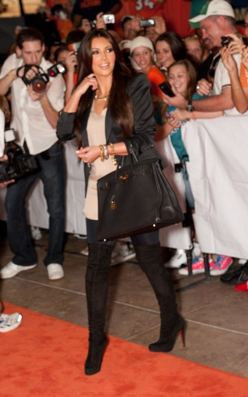 Kim Kardashian wearing LnA Olivia Gathered Bottom Leggings Christian Louboutin Monica Over The Knee Boots Hermes So Black Birkin 35 bag. Kim Kardashian Miami Dolphins game September 26 2010.