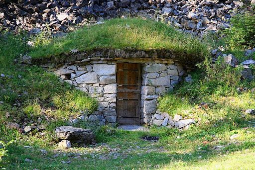 An earth berm sod style house with a nice stone exterior for Building earth sheltered homes