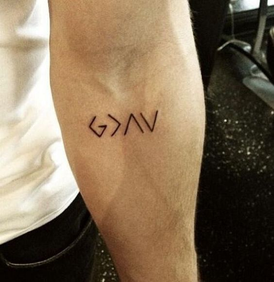 This tattoo is so simple, but the power behind it is great. It looks like just some weird letters, but its real meaning will blow your mind. The letter 'G' stands for God. The next sign is greater than, and it stands for greater than. The next two symbols are something that looks like a letter 'A' and a V. But these signs actually stand for ups and downs or highs and lows. So, the meaning of this tattoo would be: God is greater than the highs and lows.