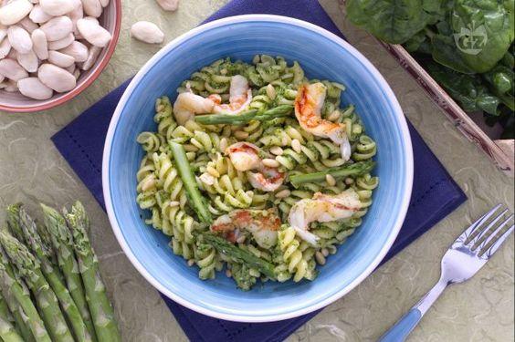 La pasta al verde con gamberetti è un primo piato realizzato con un pesto di spinaci e asparagi, arricchito con gamberi saltati.