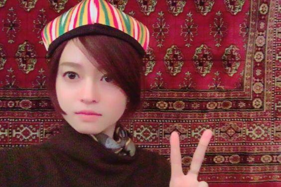 カラフルなストライプの帽子をかぶってピースをしている小林涼子の画像