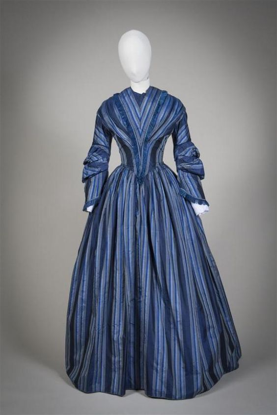 Gown of blue / white / black striped silk, garnish of blue silk fringe...circa 1855