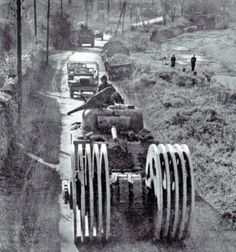 A Sherman of 6th Armored Division, equipped with huge mine rollers leading a column of vehicles by Nancy, October 1944.