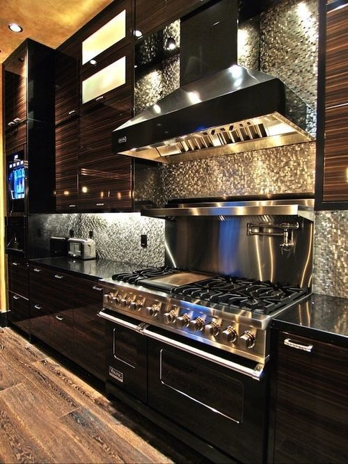 The appliances in this one seem to shimmer on their own, nevermind the shimmer of the cabinets. Plus the silver backsplash only serves to make things even more rich looking.
