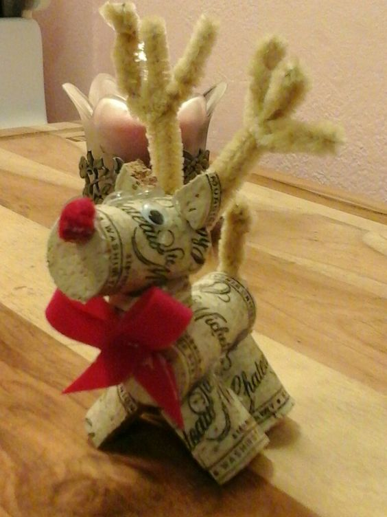 Reindeer out wine wine corks. Need 3 corks ~ 1 whole one for the body 1 for the legs, cut in half length wise & those cut in half. 3rd cut a little bit off for neck & the rest is for the head. Use 2 pipe cleaners for antlers & tail. Hot glue it together. Put on some googly eyes. I scrunched up some red felt for a nose. Cut ribbon for adornment.