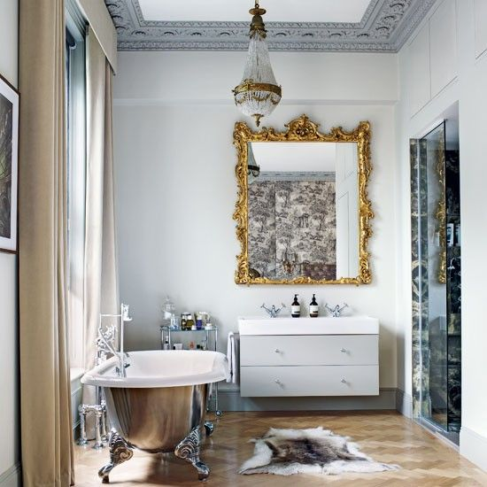Grey opulent bathroom. A silver freestanding bath is positioned in front of a large window. A trolley is ideal for holding bottles and bathroom accessories, leaving the basin uncluttered. #bathroom #toilet #shower