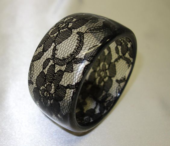 This is a vintage lucite bracelet.  It features 1 5/8 wide clear lucite walls embedded with black lace.  The bracelet is in excellent condition and