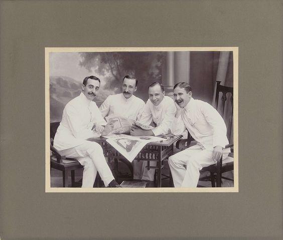 Anonymous   Groepsportret van drie heren in witte pakken voor een achtergronddoek, Anonymous, 1910  