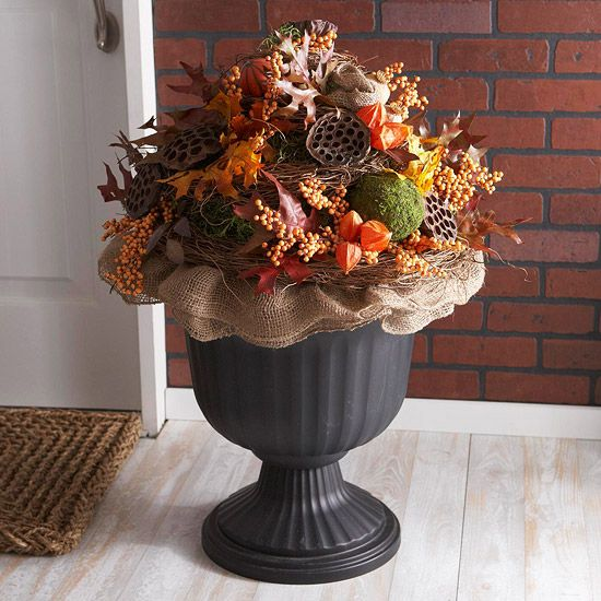Decorative Fall Urn -- Build a mound of cut plastic florist's foam pieces inside a plastic urn. Cover with Spanish moss (available at crafts stores), keeping the moss in place with green pins. Make a collar of burlap around the urn and build your arrangement with artificial leaves, berries, Chinese lanterns, dried lotus pods, and other fall favorites from the floral selection of your local crafts store. Green pins help keep everything in place.