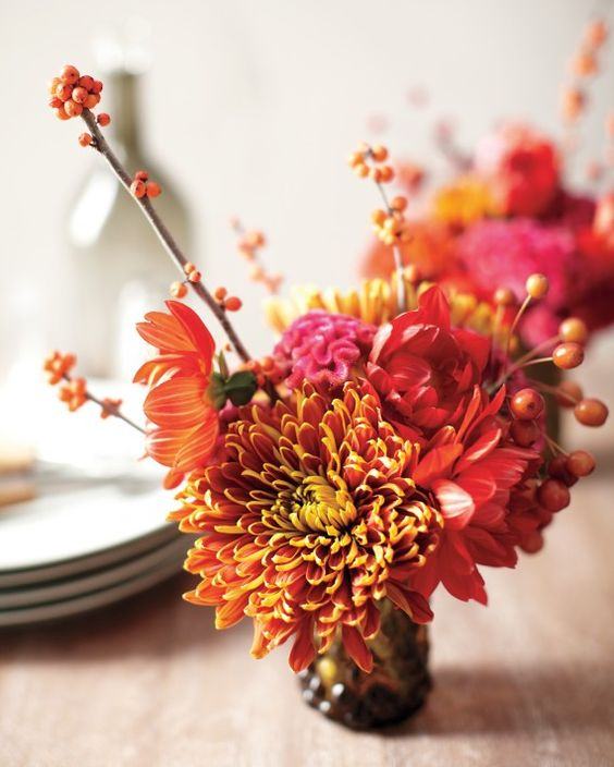 Cut the stems of a typical bouquet of late dahlias and mums from a farmers' market or corner florist, and mix the flowers with foraged crabapples and orange winterberry. Divide them among three small water glasses. The short arrangements are the ideal height for lining the center of a dinner table.