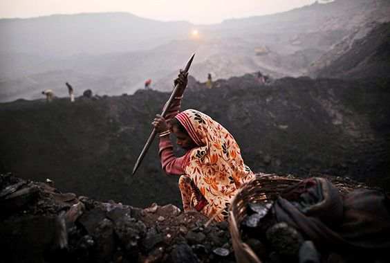 Bokapahari, India: A labourer chips away at a seam of coal