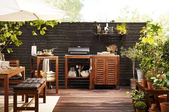 Ein gemütlicher Balkon: Tisch und Bank aus Holz, Sonnenschirm, Pflanzen und ein Holzzaun als Sichtschutz