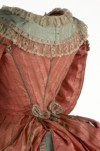 Gown detail, 1775 -1780, Spain. Linen, silk, satin, lace, taffeta, tape [Handpainted]. Round neckline has detachable cowl. Trimmed with bobbin lace linen that runs around the perimeter of the neck, front and cuffs. The same perimeter is crossed by a silk ribbon hand painted with motifs of leaves and stems. All seams are covered by a braided silk cord and shoulder pads leads draped topped with tassels.     [CE001005 ]  (c) Museo del Traj ceres.mcu.es:
